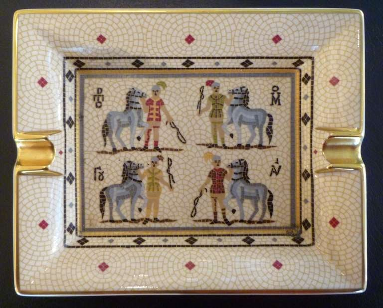 An oblong white porcelain, limited edition cigar ashtray of typical style with decoration of for horses and riders, on a cream 'mosaic' patterned background with gilt detailing. Marked HERMES PARIS to one side and MADE IN PARIS to the opposite with