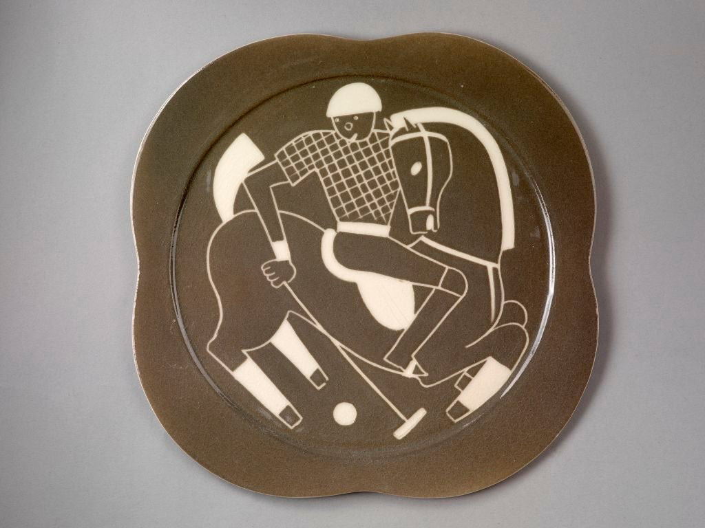 A set of twelve ceramic Art Deco plates (only ten shown) depicting polo players in action, each plate has a unique white sgraffito decoration, against a smoke-grey glaze, with scalloped edges and all are incised on the reverse with the Waylande