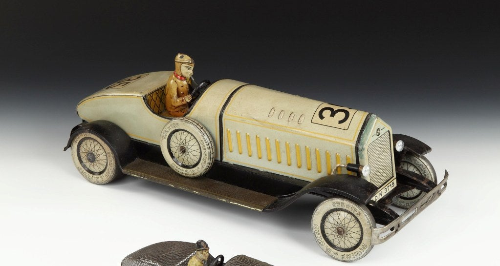 An incredibly rare tinplate stylized racing car toy by the company Johann Distler, in cream livery, with driver in traditional driving attire, lithographed detailing, marked number 35 with running board, bumpers and Dunlop 935 x 135 tyres and side