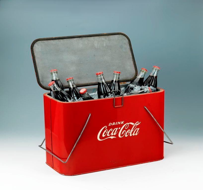 A promotional picnic cooler made by the Coca Cola Company. Hinged at the rear with a small wire latch and two wire handels. To the base marked Progress Refrigerator Co. Louisville Ky. American.