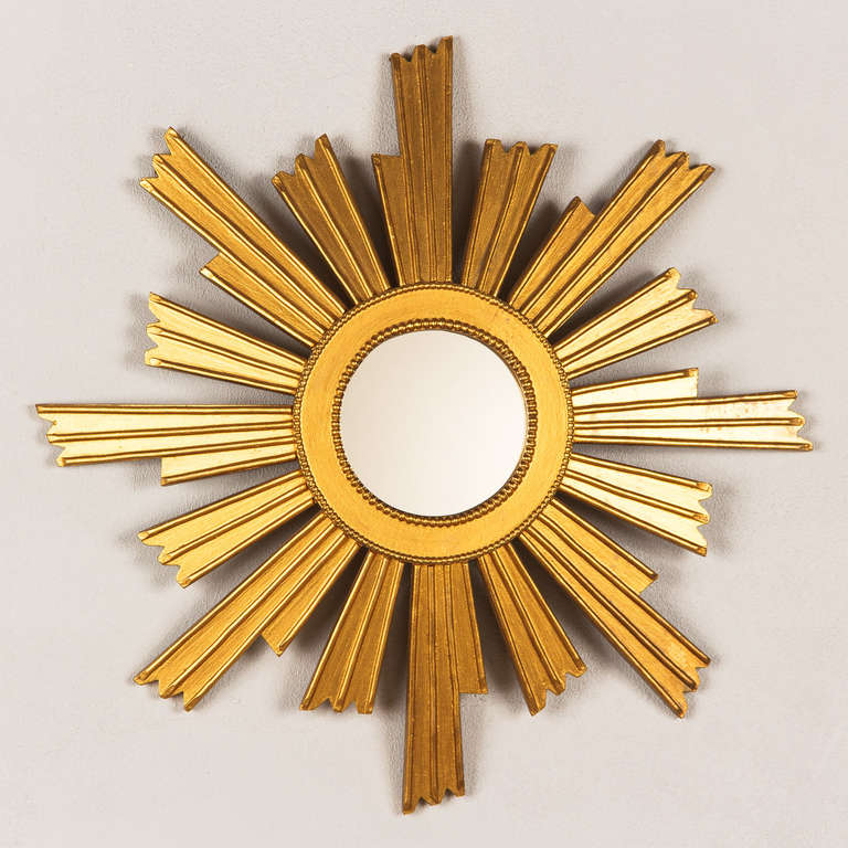 A mid-century giltwood sunburst mirror, French circa 1950. At the center is a 4.75