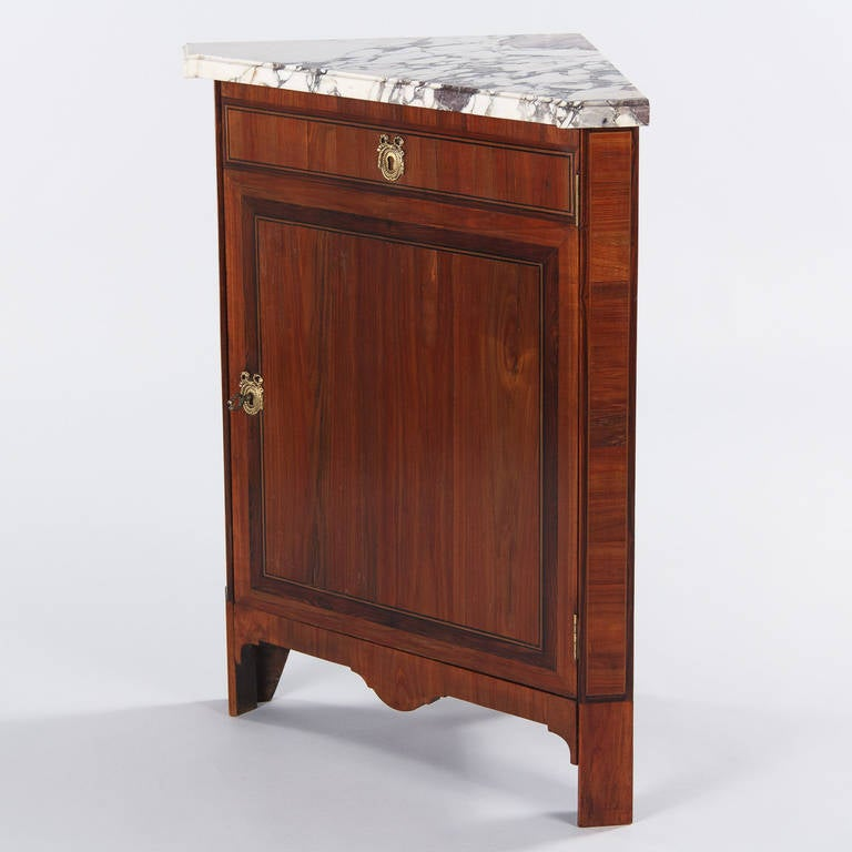 """A small corner cabinet in the Louis XVI style made of rosewood veneer with fruitwood inlaid. The single door has brass escutcheons with ribbon motifs for the key entry and the """"faux"""" drawer, the apron is scalloped and the inside has a non adjustable"""