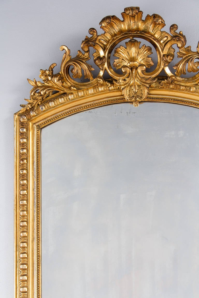 A fabulous French Louis XV-Louis XVI Transition period mirror in gold leaf with its original glass. The gilded frame has gadrooned moldings and a beaded trim around the glass. The arched top crest has open work intricate carvings in shells,