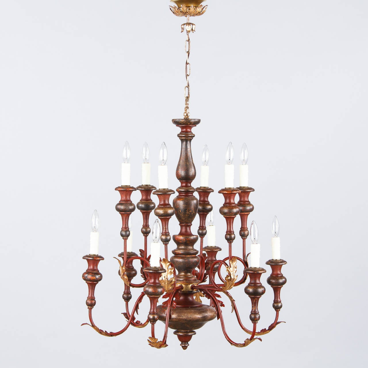 A wonderful twelve-light chandelier from Italy, circa 1920s, made of painted wood and metal with gilded metal acanthus leaf motifs. The center part is turned wood painted in faded red and bronze tones. The arms are scrolled metal painted red. The