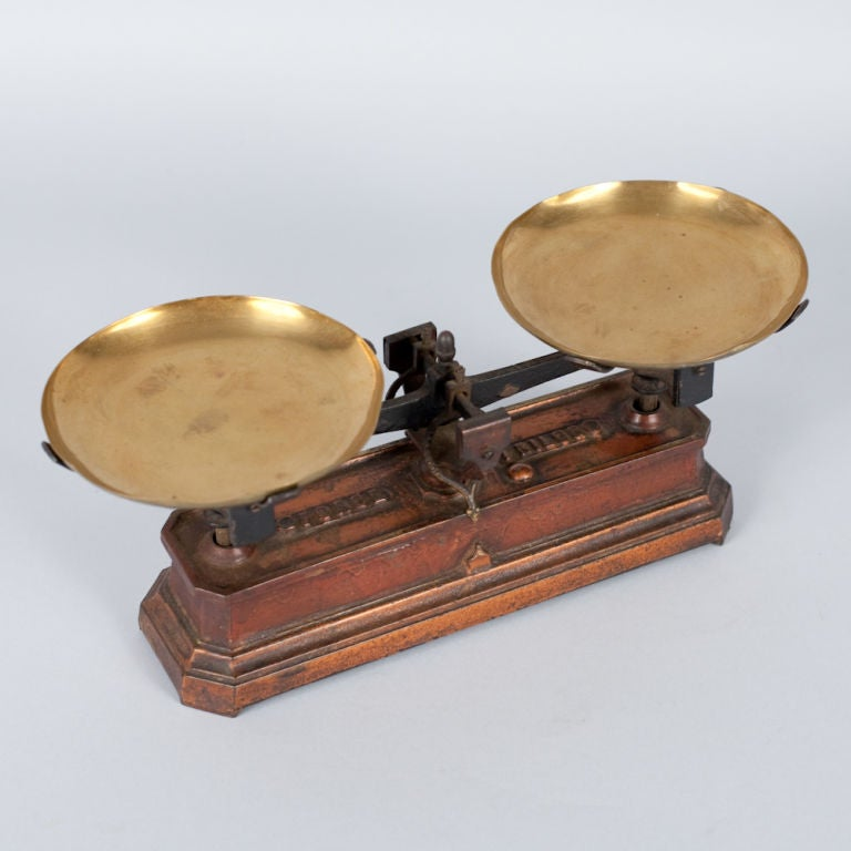 A decorative Apothecary Scale in burnt orange enamelled metal with brass plateaux.