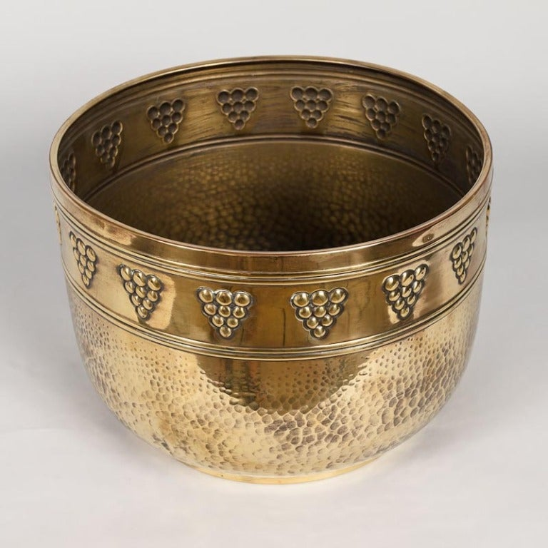 A decorative jardinere in hammered and embossed brass from the Bresse Region of France. Straight sides and a rounded bottom rest over a short base pedestal. The base has hammered texture, larger at the bottom and diminishing as you go up. Two pairs