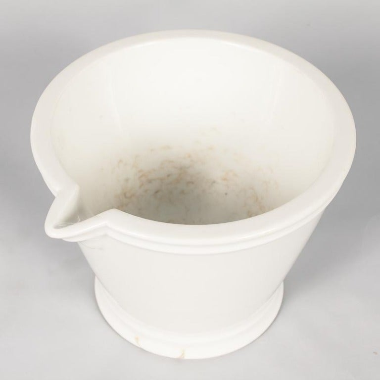 A large, glazed ceramic pharmacist's mortar and pestle for apothecary use, circa late 1800s. White ceramic form with a flared top and tapered base, molding at the foot and at the rim. The pour spot is angled and level with the rim. Smoothly glazed