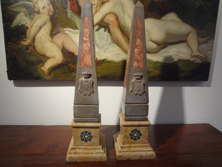 Classic pair of antique Italian marble obelisks with a crest. These Italian neoclassical style marble obelisks would look great on a console, commode, credenza, cocktail table, bookcase or on a fireplace mantel.
