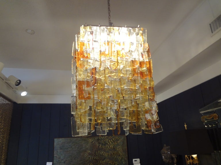 Monumental Italian Mid-Century Modern multicolored interlocking Murano glass chandelier on chrome base by Carlo Nason for Mazzega. This stunning Murano chandelier is comprised of clear, gold and yellow glass and has been newly wired for U.S.