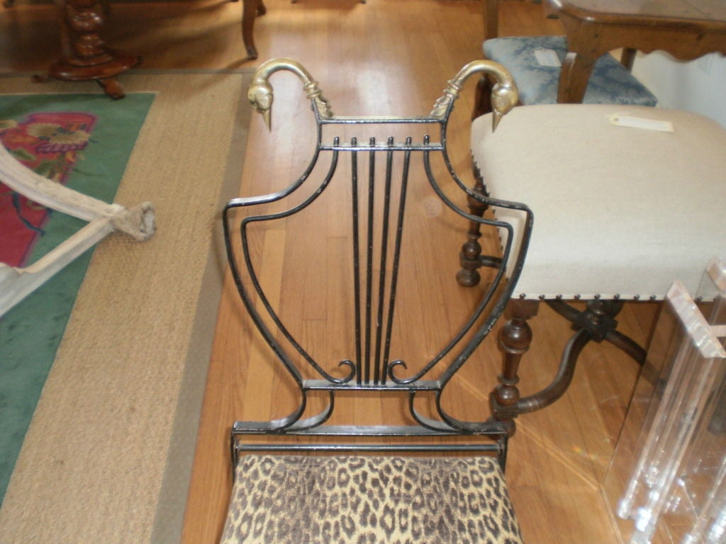 Stylish Italian neoclassical Maison Jansen inspired iron and brass lyre-back chair with swan heads and paw feet, circa 1940. Perfect accent chair, side chair, vanity chair or desk chair.