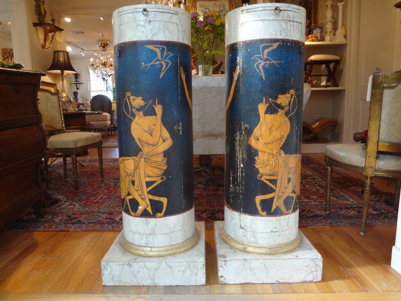 Outstanding pair of Italian Neoclassical style painted and gilt column pedestals, each with cabinet door for storage and shelf and bronze hardware. (Base dimension 15.75 inches x 15.75 inches  top 12.5 inches diameter).