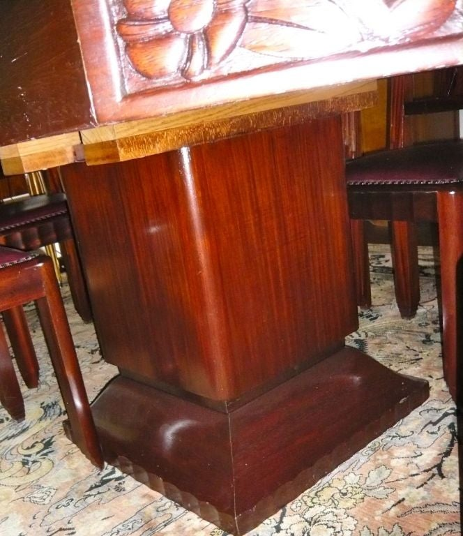 Stunning 1930s French carved and stepped dining room table and six matching chairs. High deco carvings on four facets of table and on each chair back. Made out of exotic African Padauk wood. Stepped chair feet and chair sides, with unusual center