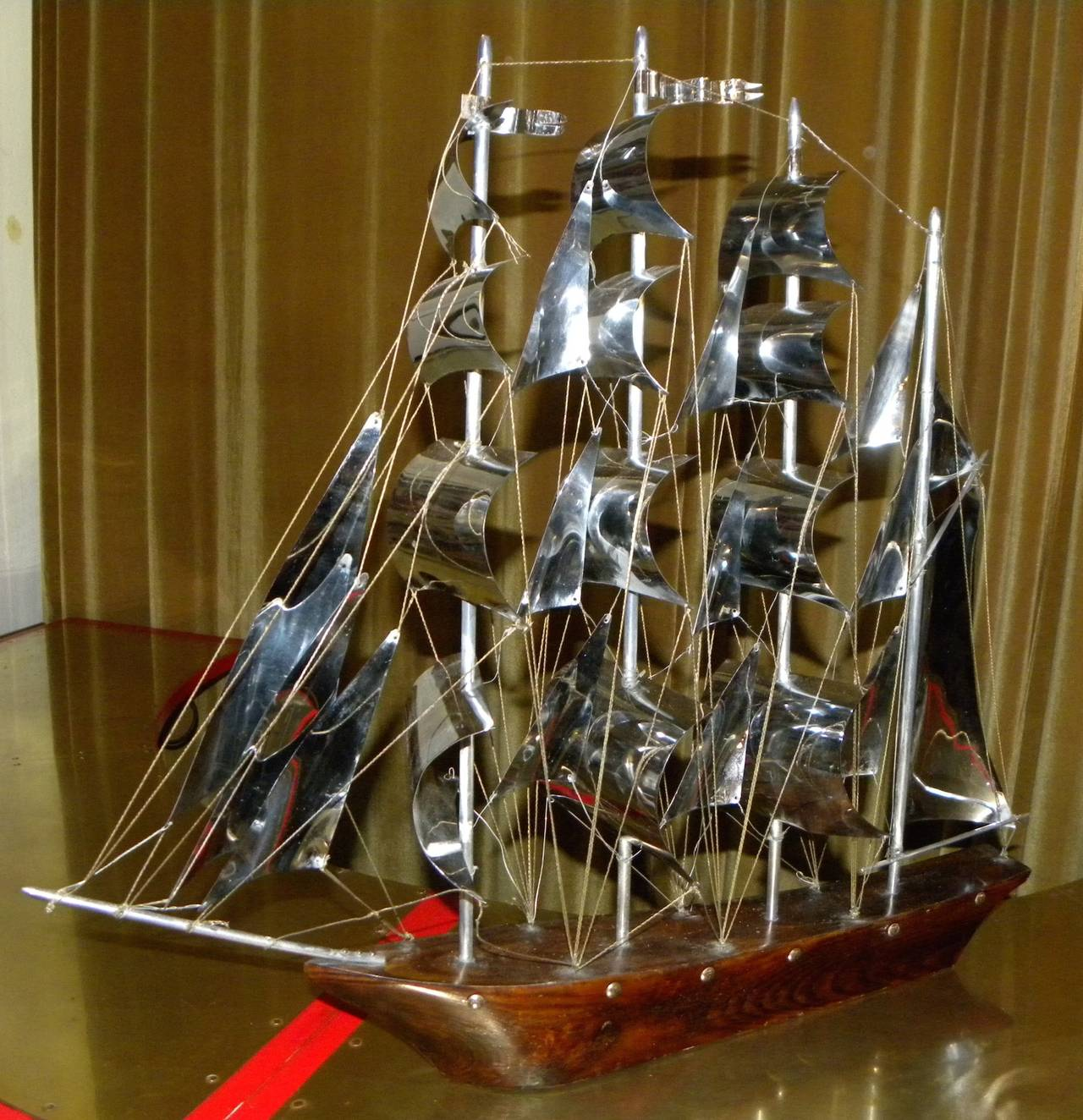 This stunning Art Deco large-scale sailboat is truly a magnificent sight. The metal is all original and in amazing condition. Solid wood base with many metal details depicting the sails, the lines and flags. This size is very large and would make