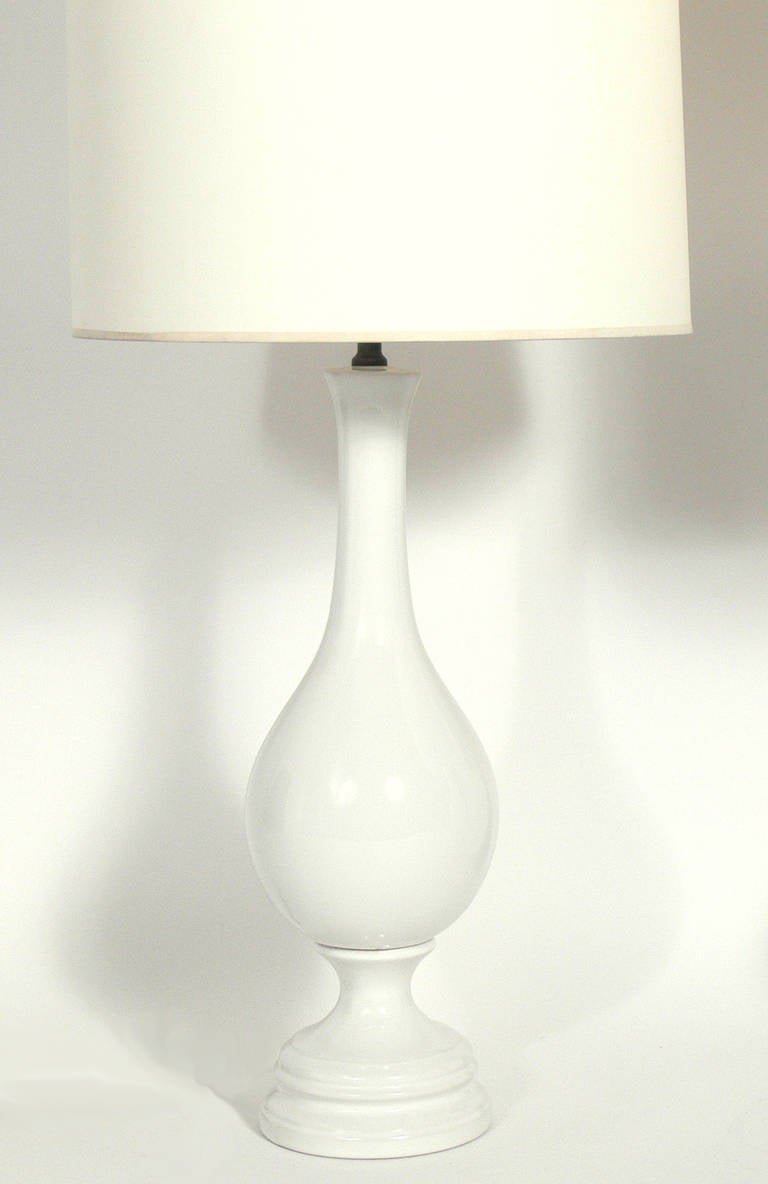 Pair of Tall White Ceramic Lamps, circa 1950s.They have a very simple, clean lined form and a pure white color. They have been rewired and are ready to use. The price noted in this listing is for the pair of lamps and shades.