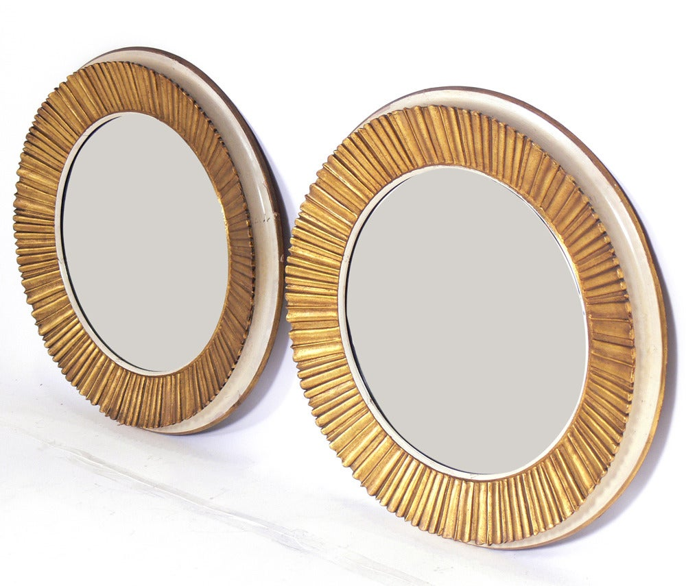 Pair of Elegant Gilt Sunburst Mirrors, probably French, at least circa 1940's, possibly earlier. They have a gilt sunburst facade with ivory color sides and gilt back trim. Wonderful original patina to both the mirrored glass and frames. They are