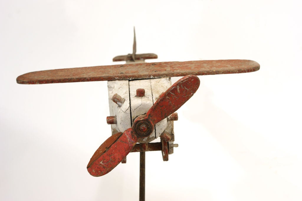 This carved wood Folk Art airplane has an amazing original paint surface and functional propeller and wheels.