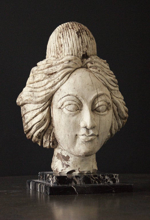 Late 19th century American carnival wagon or band organ female head carving. Very detailed wood carving with great old white painted surface. Presented on a custom marble museum stand.