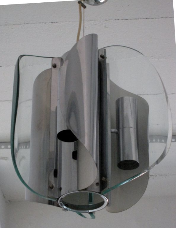 Chandelier made of a central chromed tube housing a bulb. Attached are 3 large curved thick pieces of glass and curving in the opposite direction 3 sheets of chromed metal with a tube in each housing 2 bulbs, one going upward, one downward.  An
