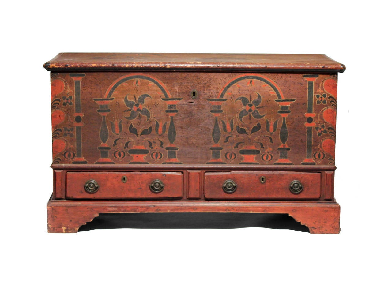 A rare and bright blanket chest in brilliant reds contrasted with blacks. The decoration is nicely painted with urns and flowers flanked by pillars and hearts on the corners. There is decoration on the sides and traces of decoration on the top. It