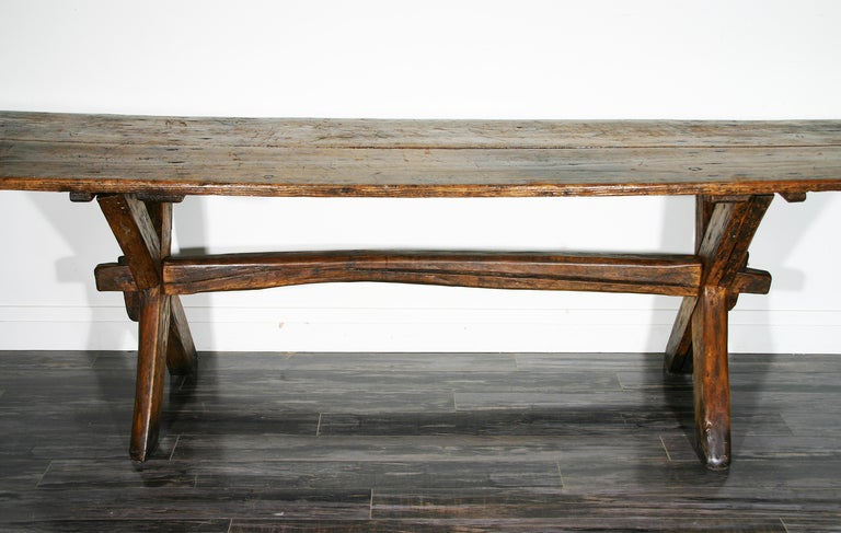 """A Rare Late 18th/ Early 19th Century Sawbuck Dining Table, having a two plank pine top to a chestnut """"X"""" base.  Good original distressed surface; breadboard ends and traces of original paint to base.  Original cleated top; fine overall wear;"""