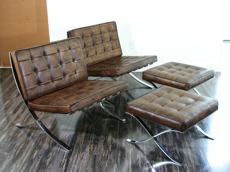 A Pair Of Vintage Barcelona Chairs With Matching Ottomans; Upholstered In  Dark Brown Distressed Leather