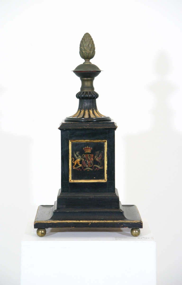 An English early 19th century Regency period painted and parcel-gilt newel post. Each side with an individual painting including a coat of arms, a dragon and an ostrich; the carved, fluted top terminating in an acorn finial. Now raised on gilded