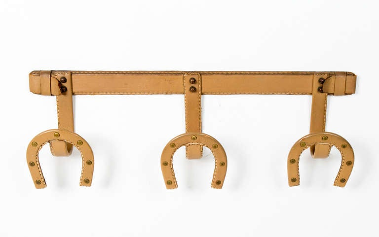 Unusual  stitched beige  leather  coat hanger by Jacques Adnet in the form of three horse shoe hooks.