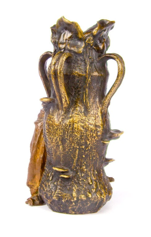 "Carl Kauba, Antique Bronze ""The Goose Girl,"" figural vase depicting a naturalistic trunk form with leaf rim and four loop handles; at the base is a young maiden, leaning on a cane with a goose at her side. C. KAUBA signed on multiple places."