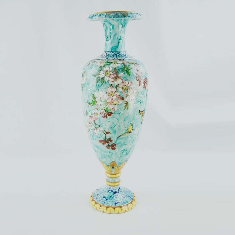 French Art Nouveau elongated baluster form Majolica vase with everted lip raised on double ring stem over floral design base bordered with serpentine motifs. The front view portrays gilt butterflies fluttering amid prunus branches; the reverse is of