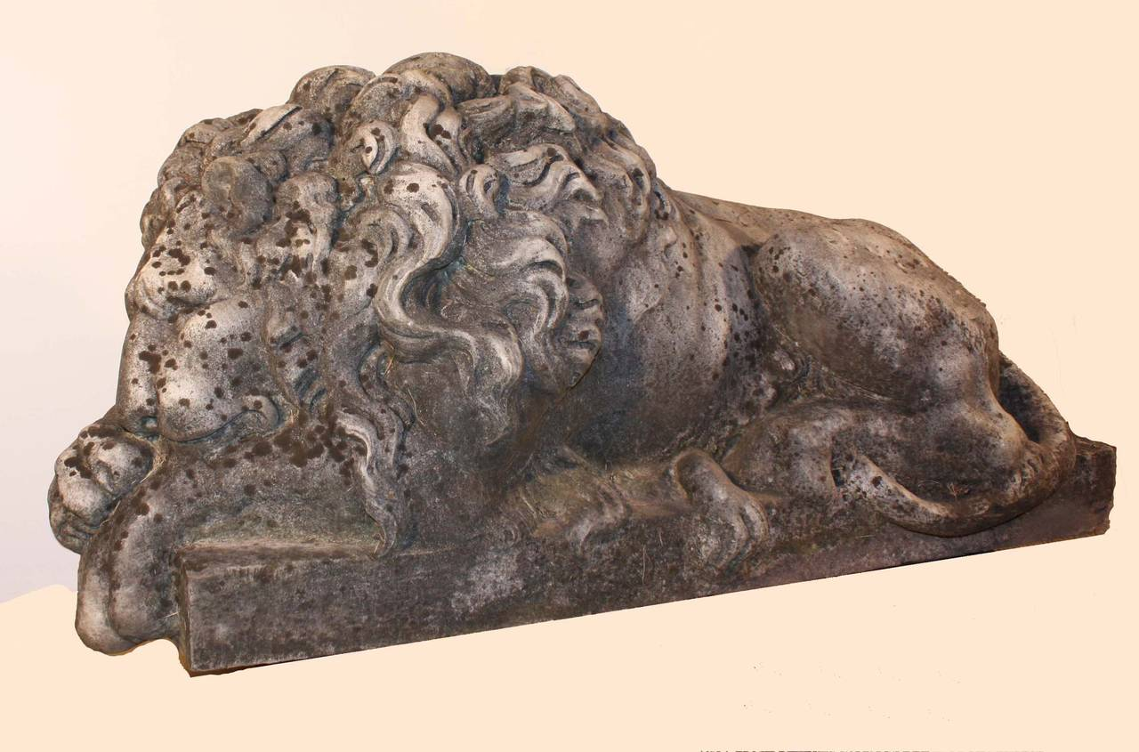 A fine pair of antique Italian carved marble recumbent lions. The originals, famous guardians of the tomb of Pope Clement XIII, were sculpted by Canova. They were much copied in various sizes from bookends to lifesize and often were bought by