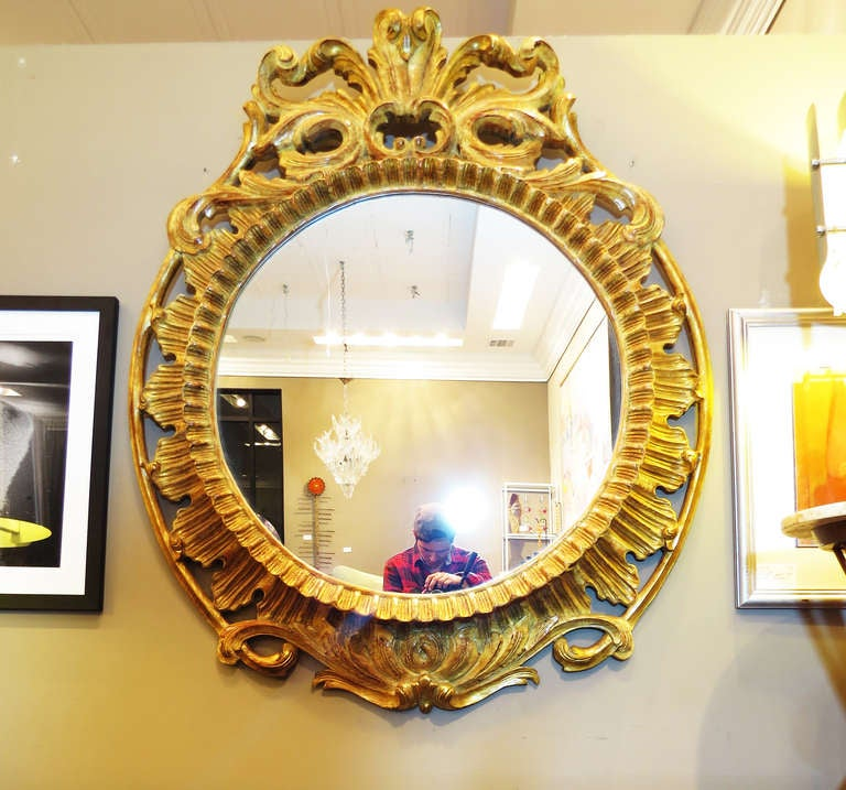 Beautiful round mirror with carved wood frame. Very intricate craftsmanship throughout.