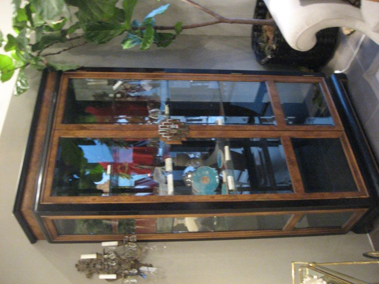 Beautiful Asian style vitrine with light walnut finish and dark finished frame. Features glass doors and sides. Also has brass, decorative pulls.