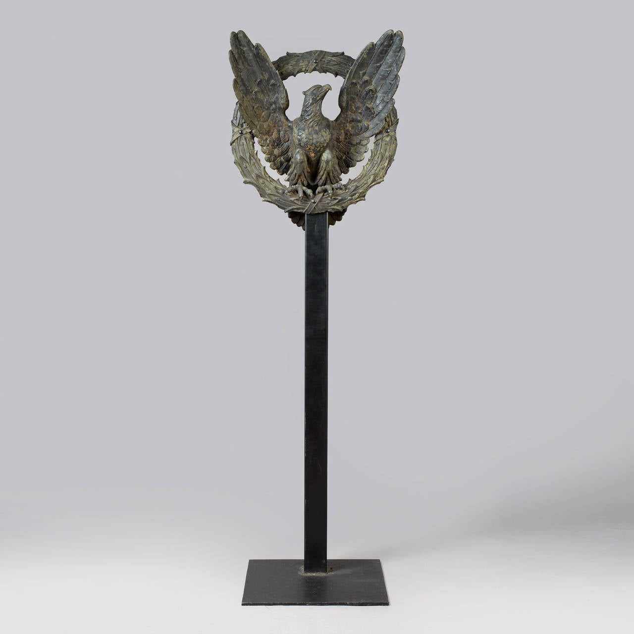 American. circa 1880-1910. Cast iron, patinated. The full body hollow cast eagle figure is mounted within a concave cast laurel wreath. Condition: Fine condition, traces of black paint now showing with a weathered patina. Mounted on contemporary