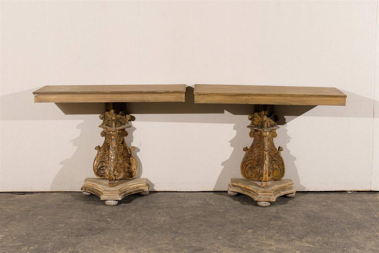 This Italian 19th century console table is made of a richly carved and decorated wooden pedestal, supporting its custom-made wood top. It stands on a concave triangular-shaped base, supported by bun feet. 