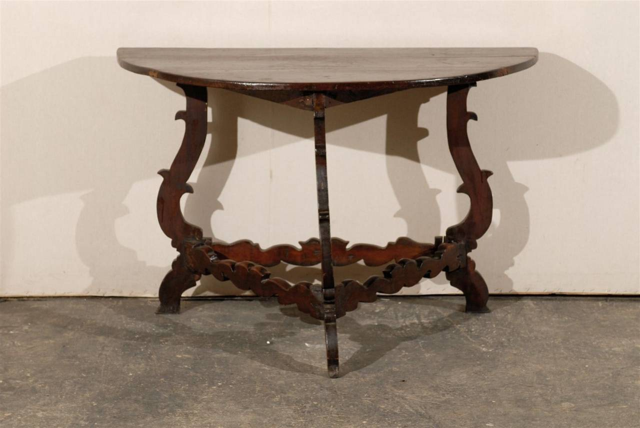 An Italian 18th century richly carved wooden tripod base demilune table.