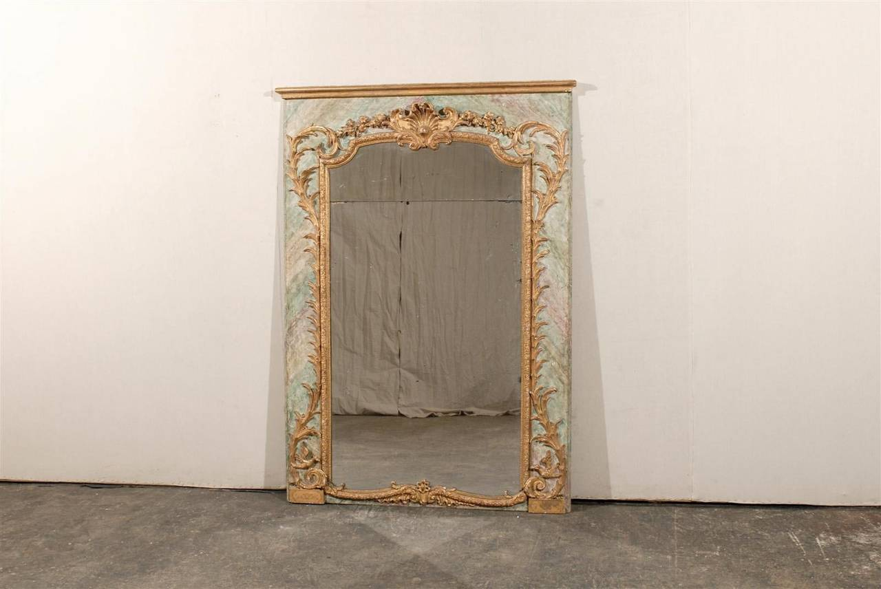 An Italian exquisite late 18th-early 19th century rocaille style wooden mirror with gold gesso and delicate floral and leaf carvings. The faux-marble frame surrounds the delicate gilt carving including rinceaux volutes, shell and flowery swag at the