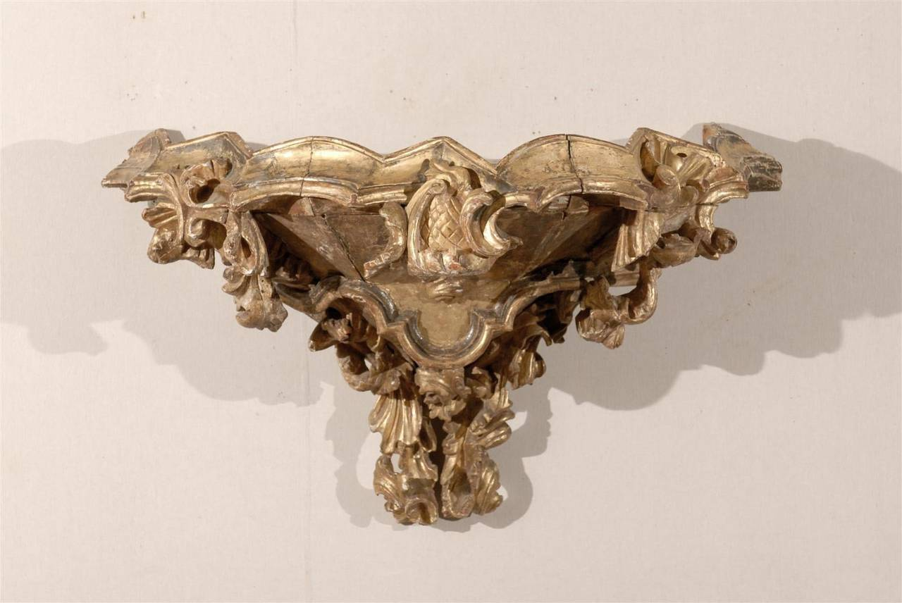 An Italian 18th century gilded bracket. This large size Italian Rococo style bracket features an abundance of decor associated to a very curvy Silhouette. The richly carved and gilded bracket. The top of the bracket is nicely delimited on the sides