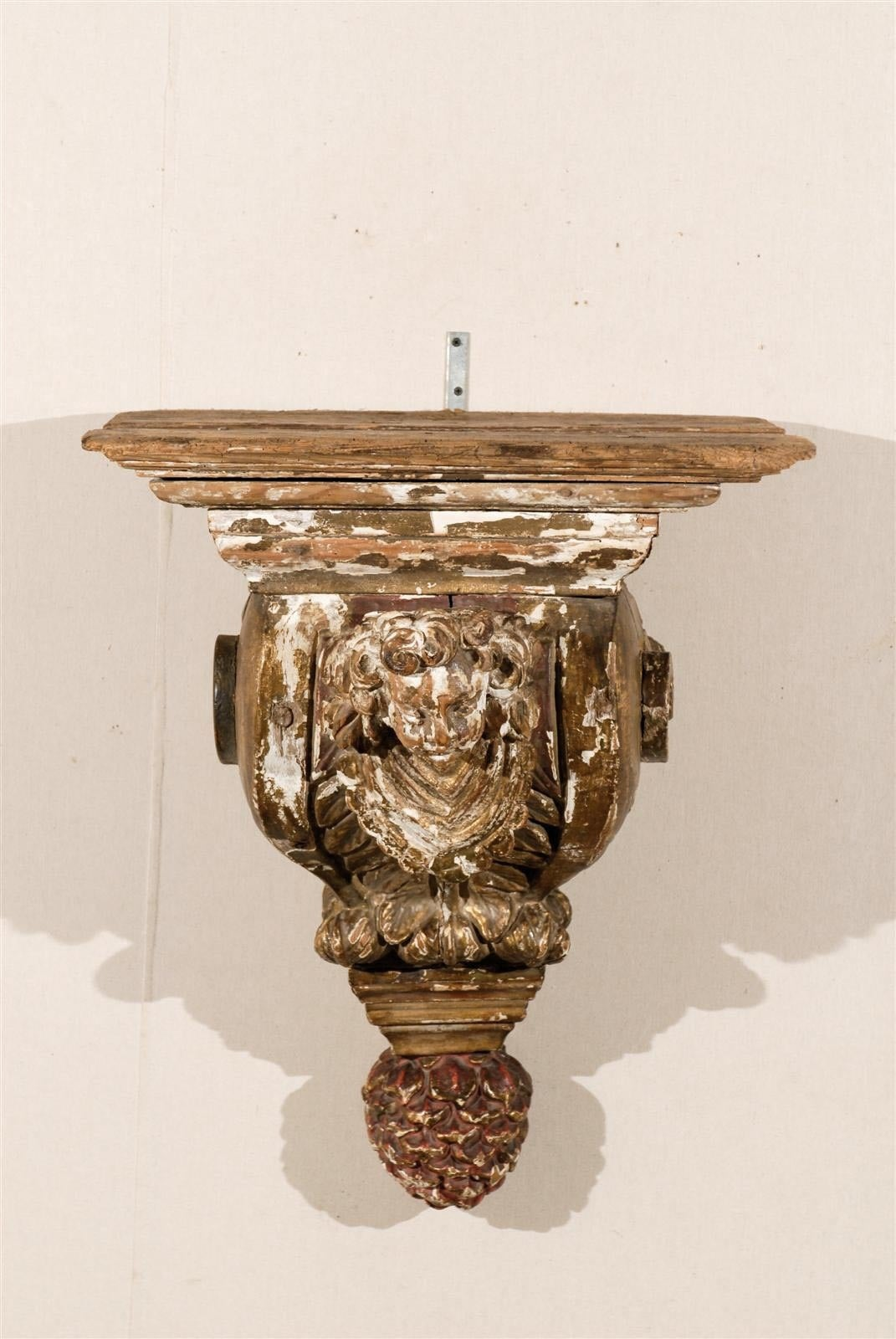 An 18th century architectural gilded and painted wood bracket with carved angel and pine cone finial.
