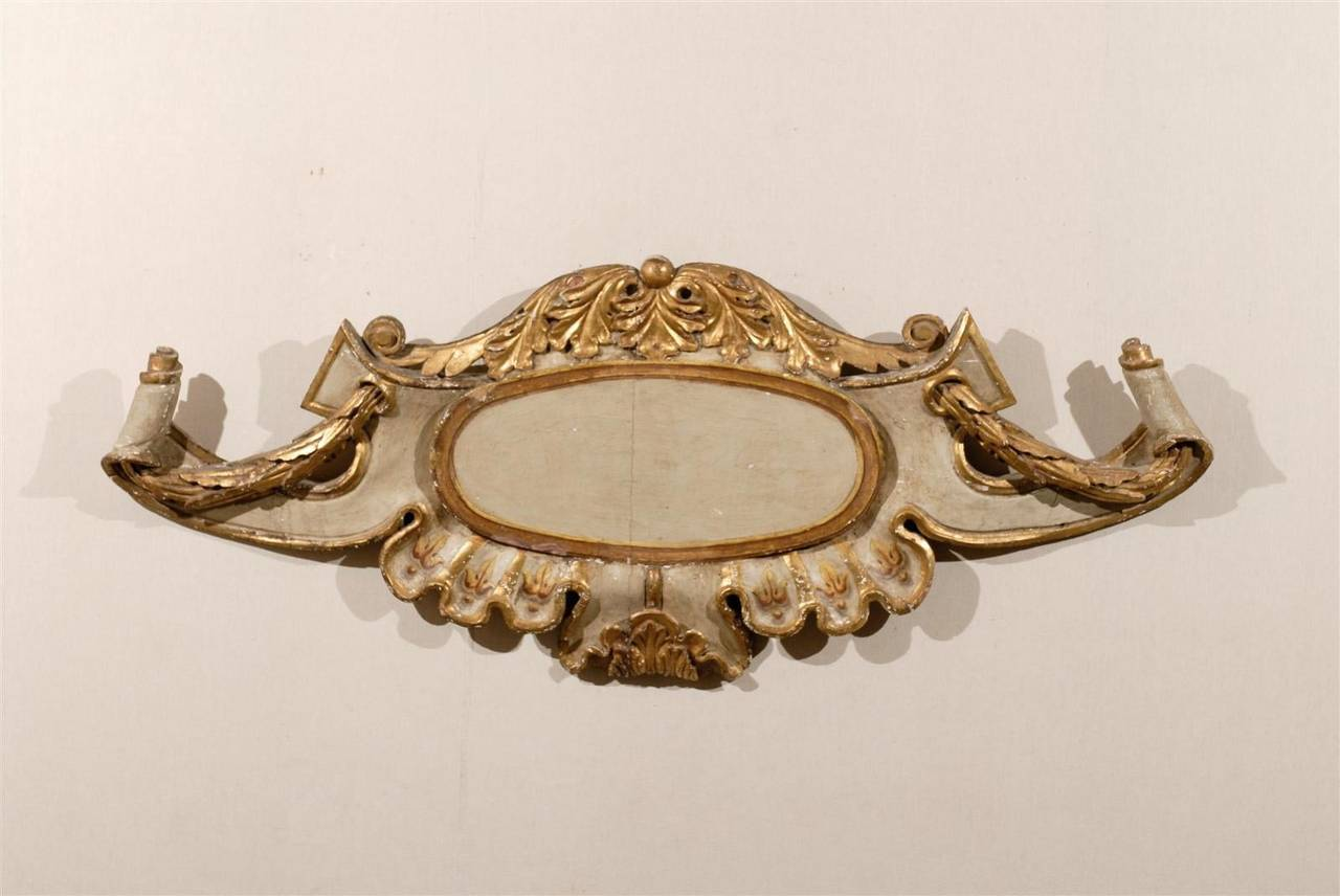 An exquisite 18th century Italian gilded and painted wooden wall plaque. This Italian large size wall decoration features a central cartouche, surrounded by a variety of motifs: reminiscent of the Baroque period, volutes and scrolls flank the sides