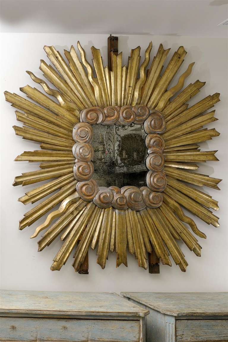 An Italian sunburst mirror of large size. This Italian early 19th century mirror features a more unusual square shape with elegant cloudy motifs surrounding the antiqued mirror in the center and a variety of alternating gilded sunrays. Nowadays, it