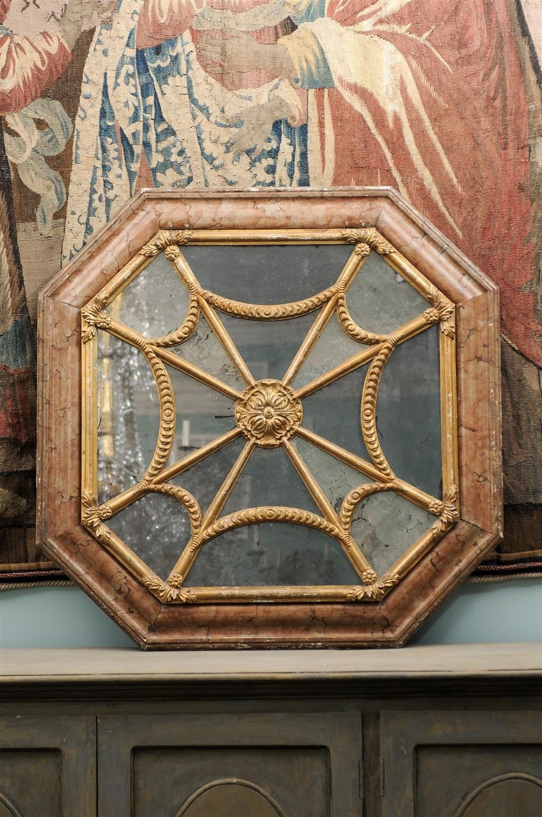 A 19th century exquisite Italian octagonal mirror with faux marble frame and original glass.