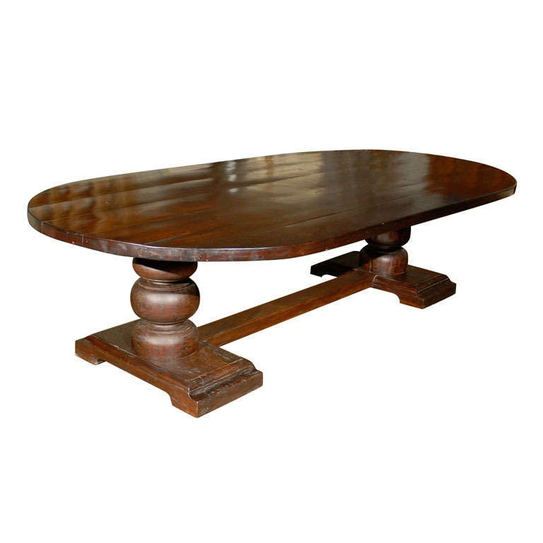 Oval dining room trestle table with hand carved base for