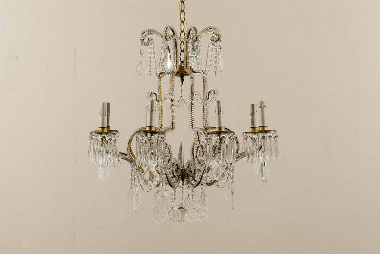 A pair of Italian crystal eight-light chandeliers. Each chandelier has a central spear and the arms are decorated with crystal beading all along. The crown part is made of eight scrolled arms, from which pendeloque crystals hang. In the lower part,