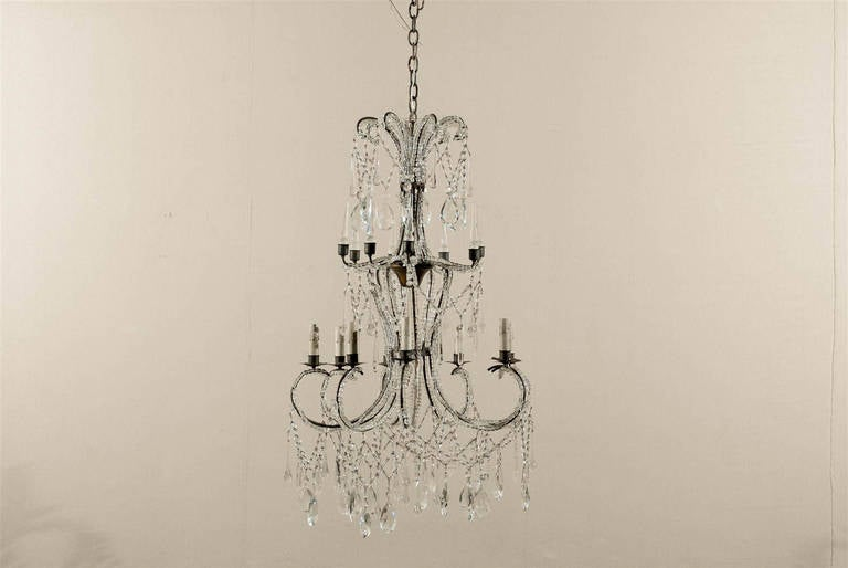 This Italian eight-light crystal chandelier is made of a succession of levels leading your eye down to the dance of crystals happening in its lowest part.  It all starts with the crown from which are hanging a circle of Swedish drops. Your eye now