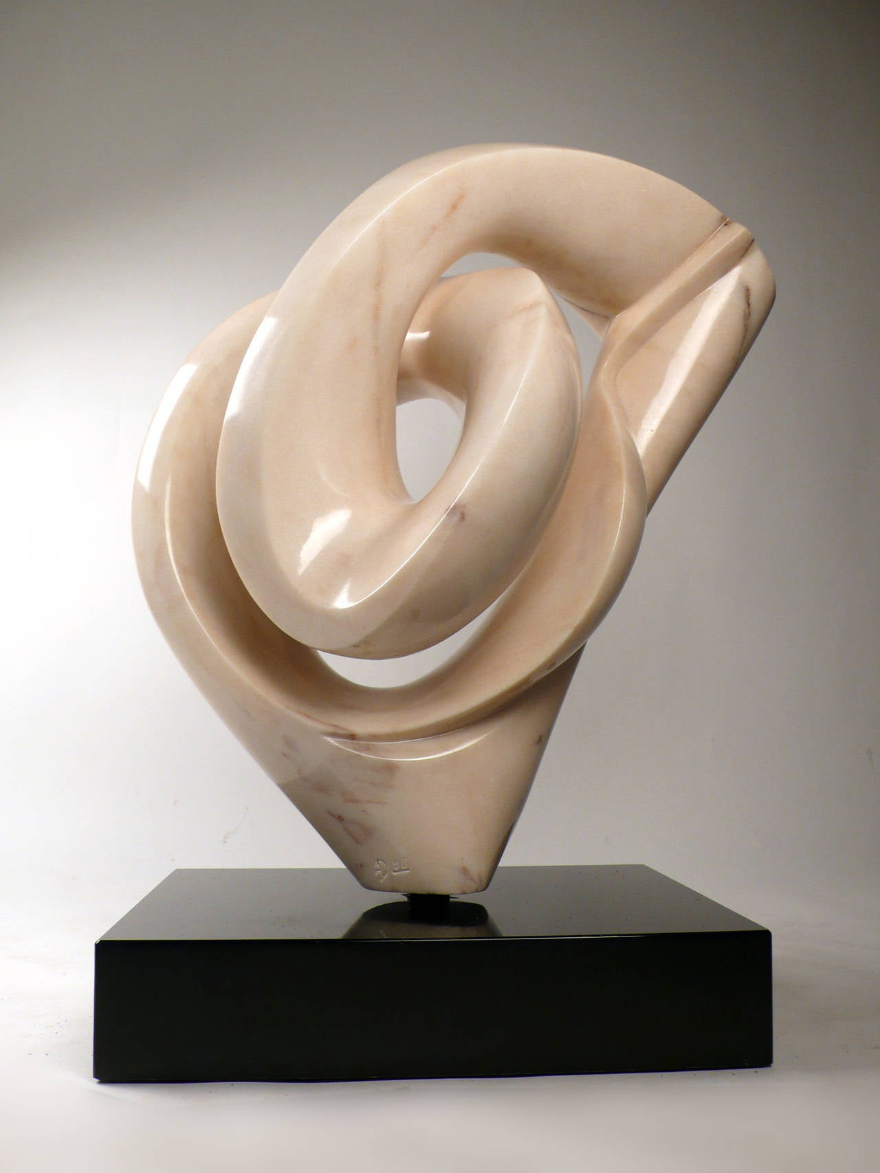 Solid 'Aurora marble' abstract direct carved sculpture from the estate of a private collector in the Florida Keys.  This sensual form is attached to a solid black marble base with brass fittings. The entire form can be rotated 360 degrees. The