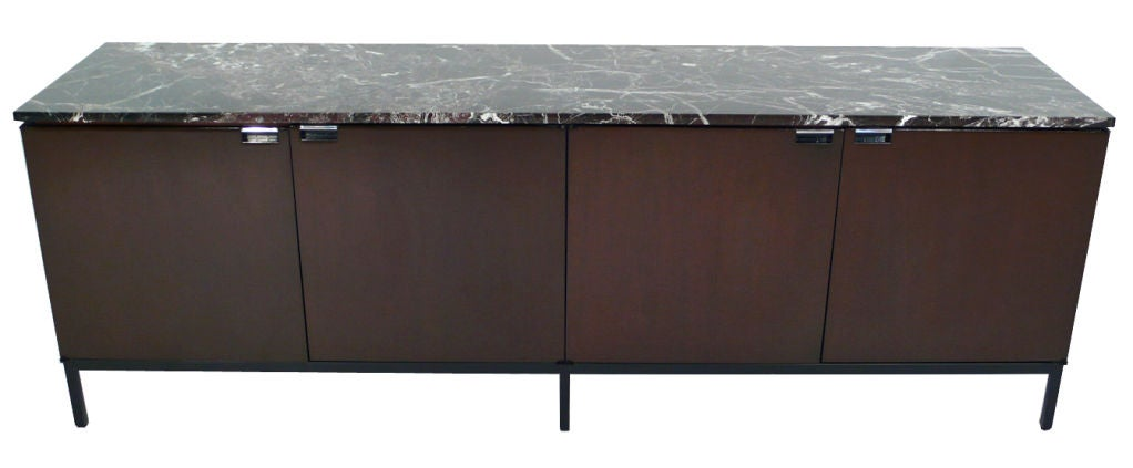 Stunning imported Florence Knoll designed credenza with original Italian marble tops. Four dark mahogany finished doors open to reveal a total of eight complimentary oak shelves. Custom black lacquered steel bases. Made by Knoll in Italy for the