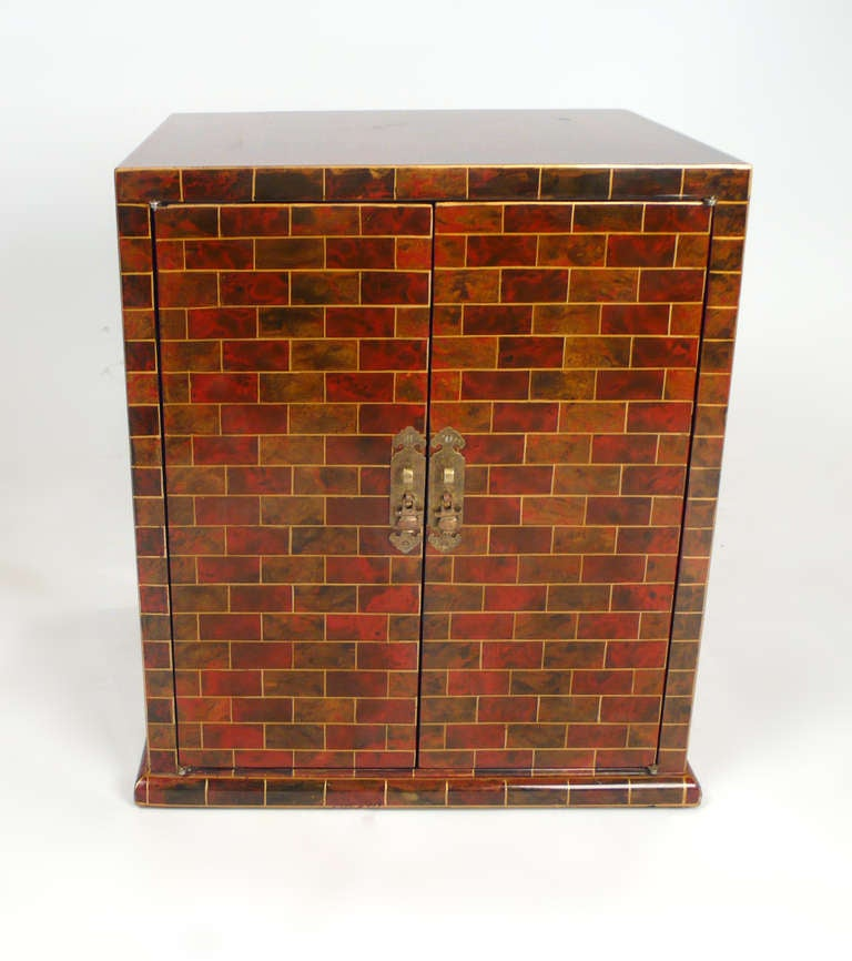 Beautiful hand-painted small chest by Maitland Smith, faux brick design. The chest is in very good original condition. Doors open to reveal an adjustable shelf.
