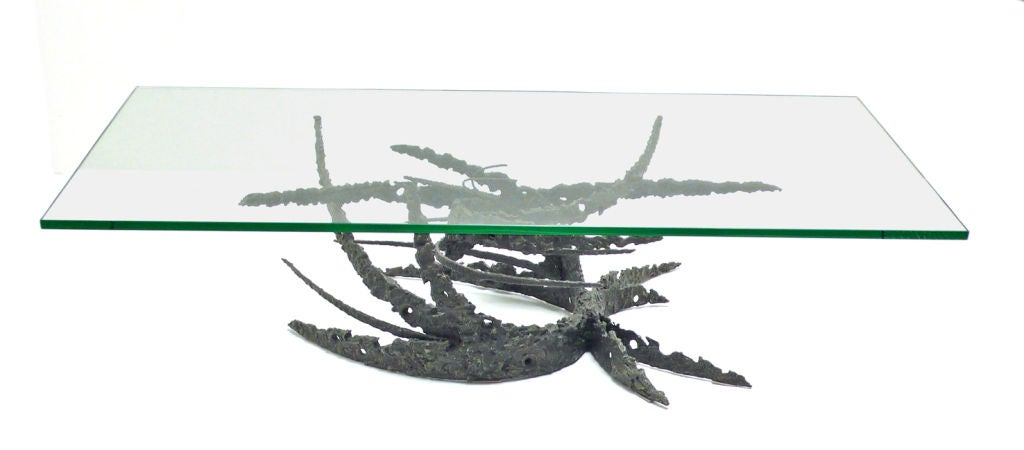 "Torch cut bronze base and glass top coffee table by California artist Daniel Gluck. This table was called the ""swirl"" table and was the same table that Bob Hope ordered for his architecturally significant Palm Springs home."