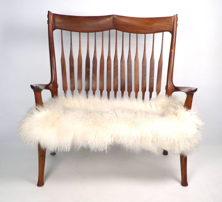 Hand carved Walnut Settee designed and fabricated by David Hentzel who was an apprentice to Sam Maloof and worked in his studio for a time. Masterfully constructed in the manner of Maloof but with its own identity. Not a copy but definitely in the