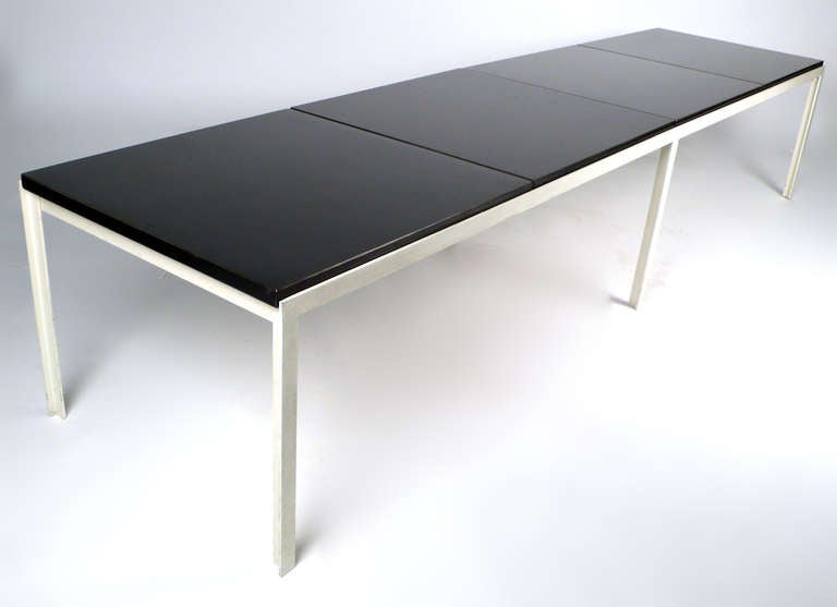 Early Florence Knoll 'T-Angle' table bench with original black laminate tops. Would serve well and an oversized coffee table or cocktail table but it is built in a way that would easily support the weight of 4 adults sitting on it. Scarce to find in